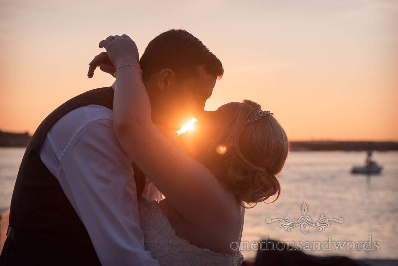 RNLI College wedding photographs Bride and groom kissing with sunset love heart