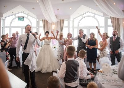 Singing waiter getting everyone involved at Sandbanks Wedding Photographs