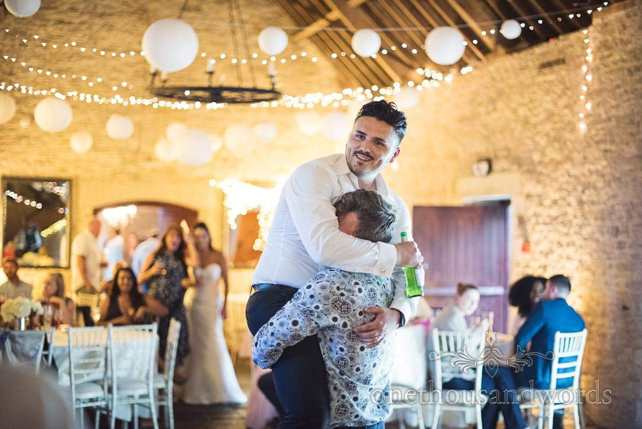 Smiling groom gets taken for a dance at Courtyard Wedding