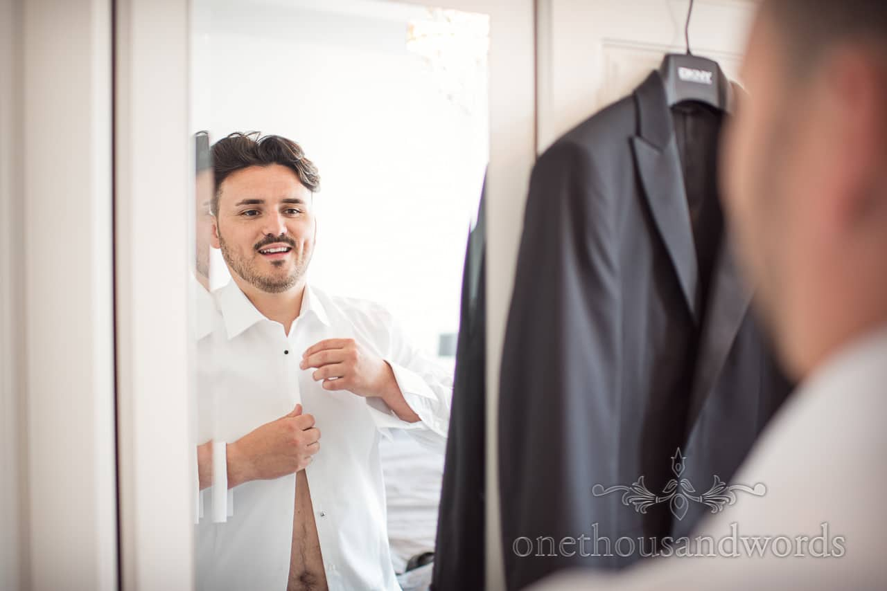 Smiling groom in mirror from morning of Country Courtyard Wedding