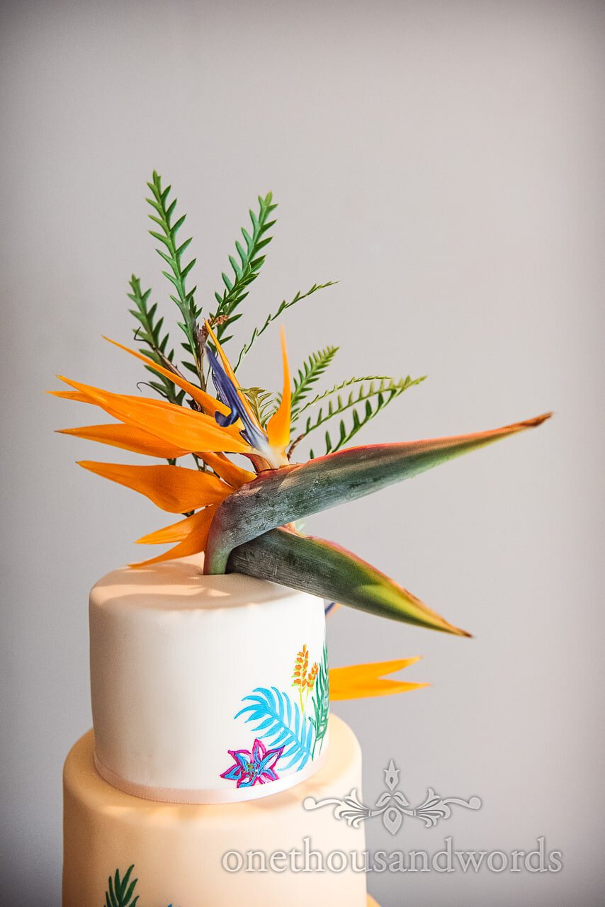 Strelitzia 'Bird of Paradise' flowers on wedding cake decorated with painted flowers