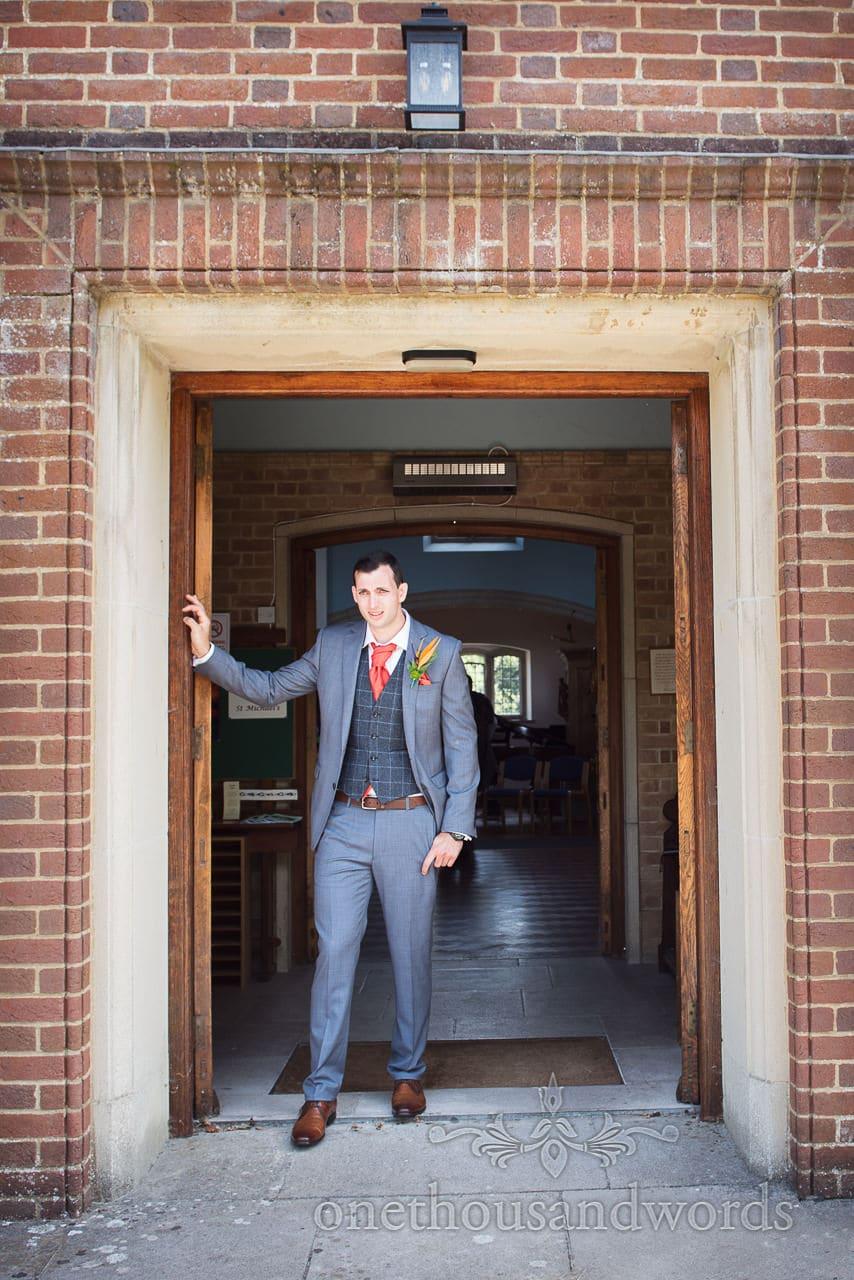 Very nervous looking groom waits outside red brick church wedding venue
