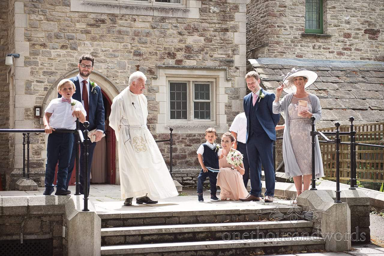 Vicar and wedding party wait outside St Marys church wedding venue in Swanage