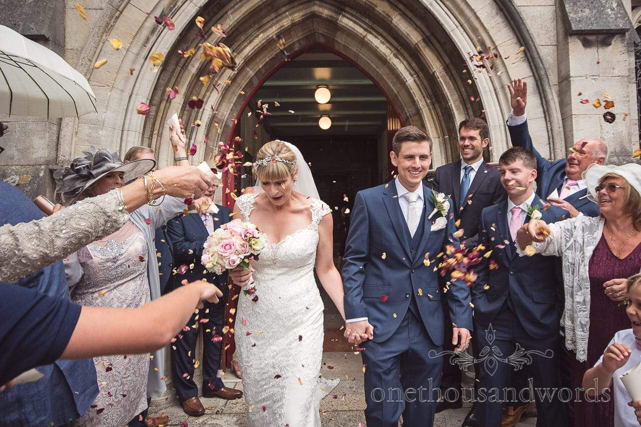 Wedding confetti photograph outside St Marys Dorset stone church in Swanage