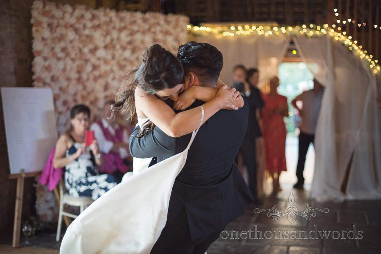 Wedding couple embrace during first dance at Country Courtyard Wedding