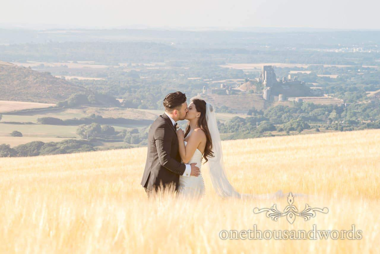 Wedding couple kiss in countryside field overlooking Corfe castle in Dorset