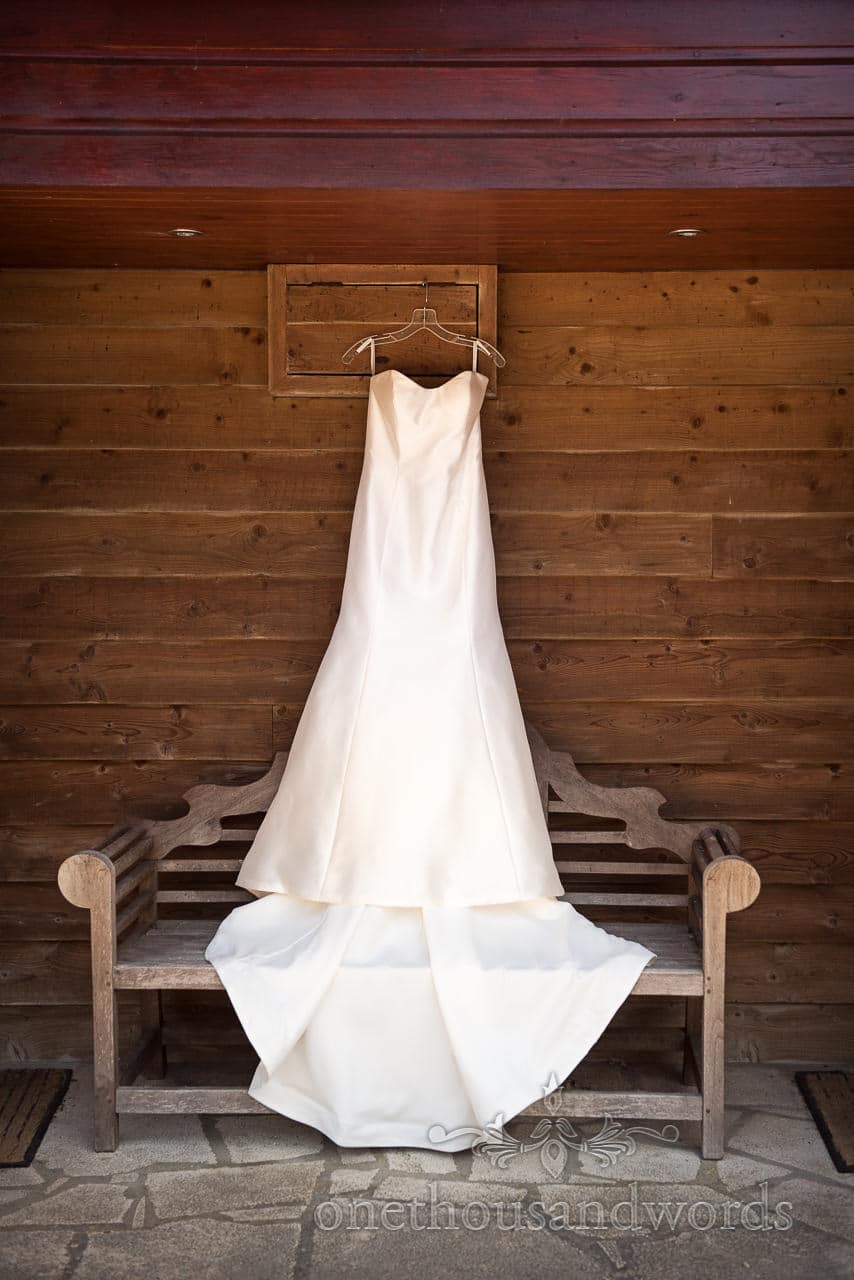 Wedding dress hangs against wood cladding at Country Courtyard Wedding