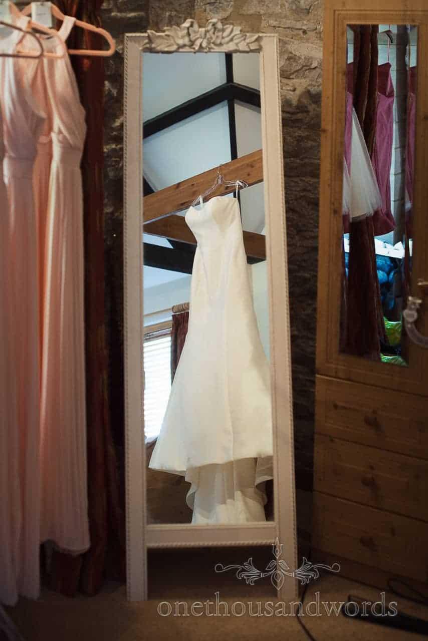Wedding dress hangs on beam from Courtyard Wedding