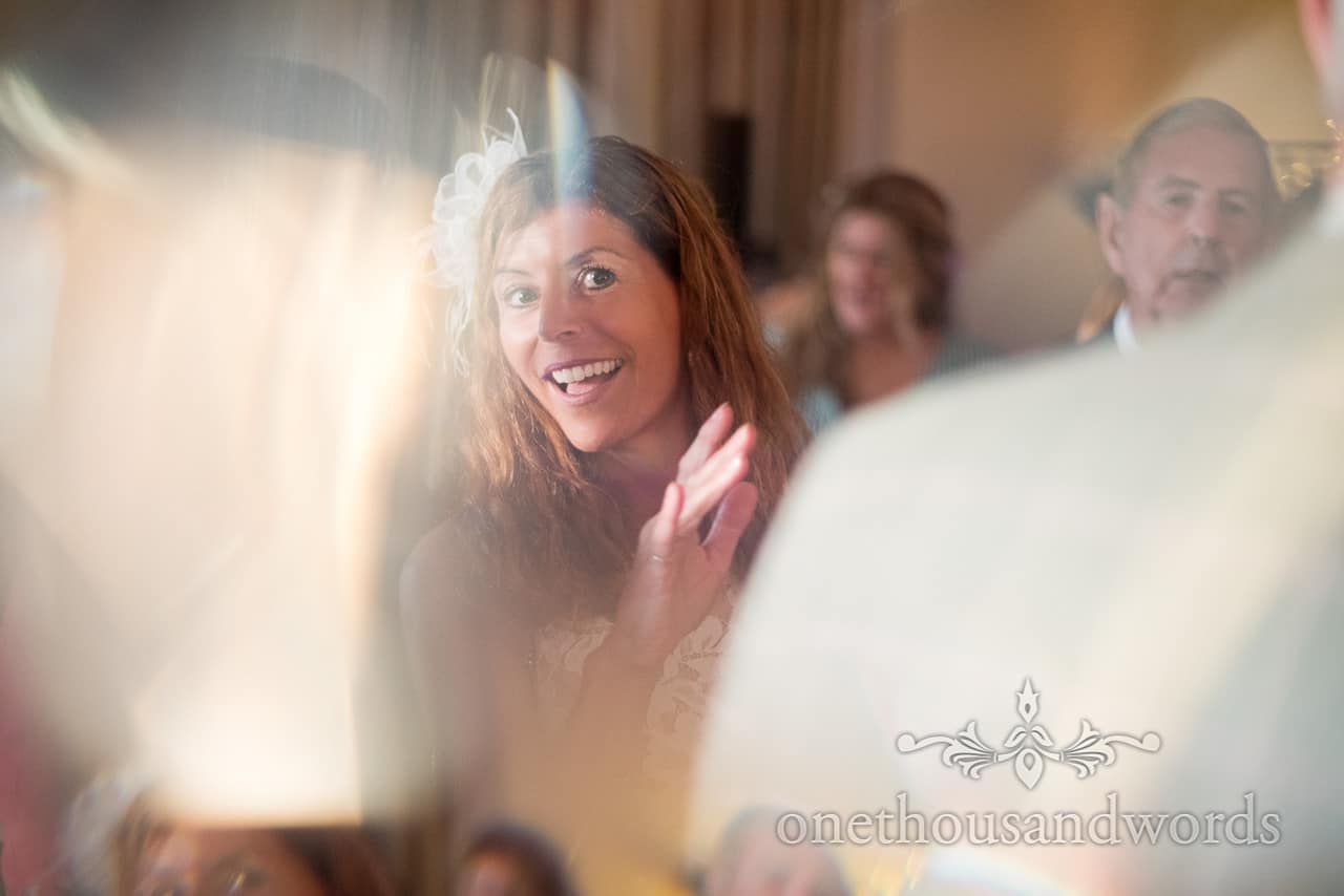 Wedding guest dances in the reflected sunlight at Harmans Cross Village Hall