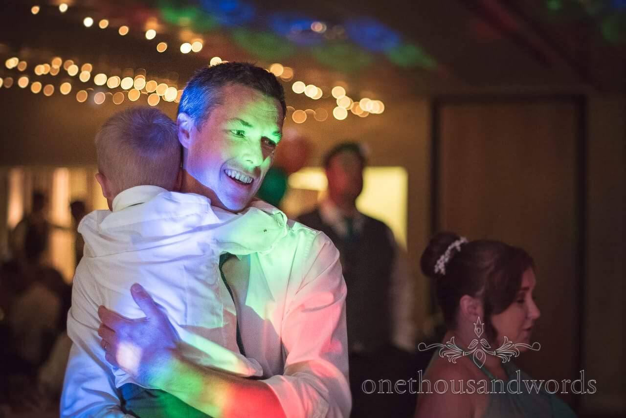 Wedding guest dances with his son at RNLI College wedding evening disco