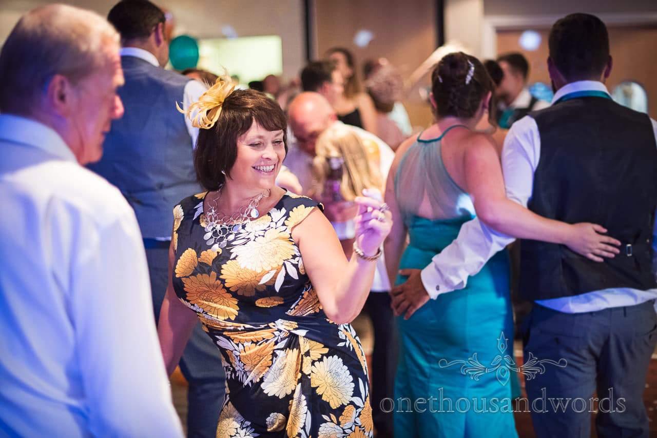 Wedding guest in floral dress dances at RNLI College Wedding evening disco