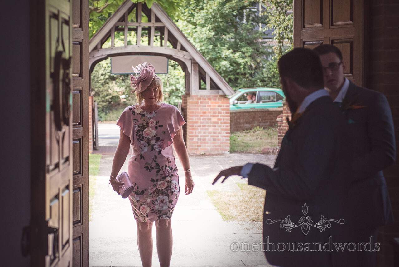 Wedding guest in pink floral dress arrives at St Michaels church wedding venue