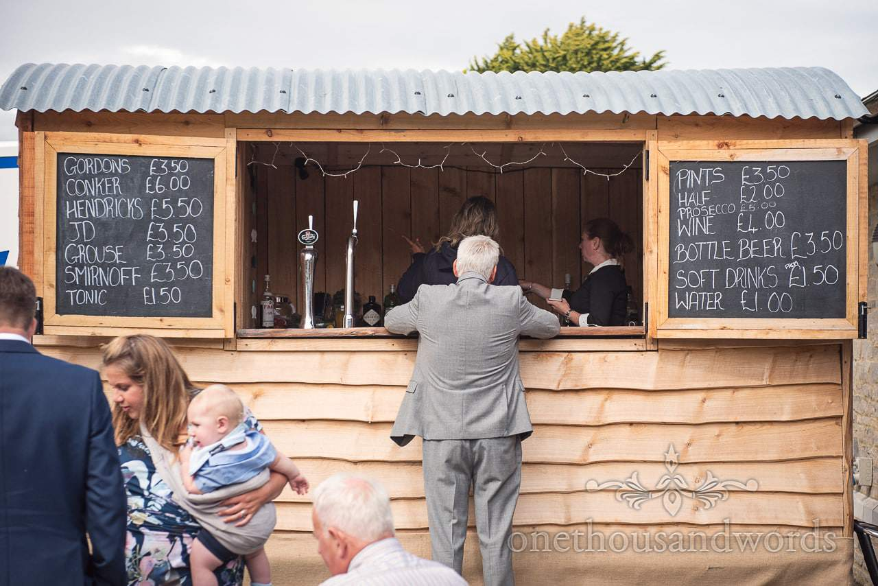 wedding guest orders drinks from A&D mobile bars wooden horsebox
