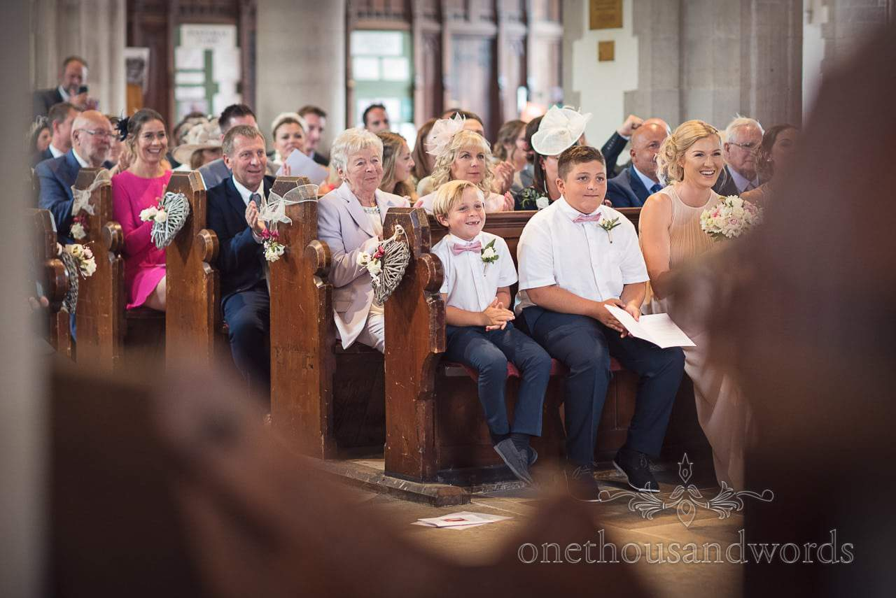 Wedding guests in church pews smile and applaud during wedding ceremony