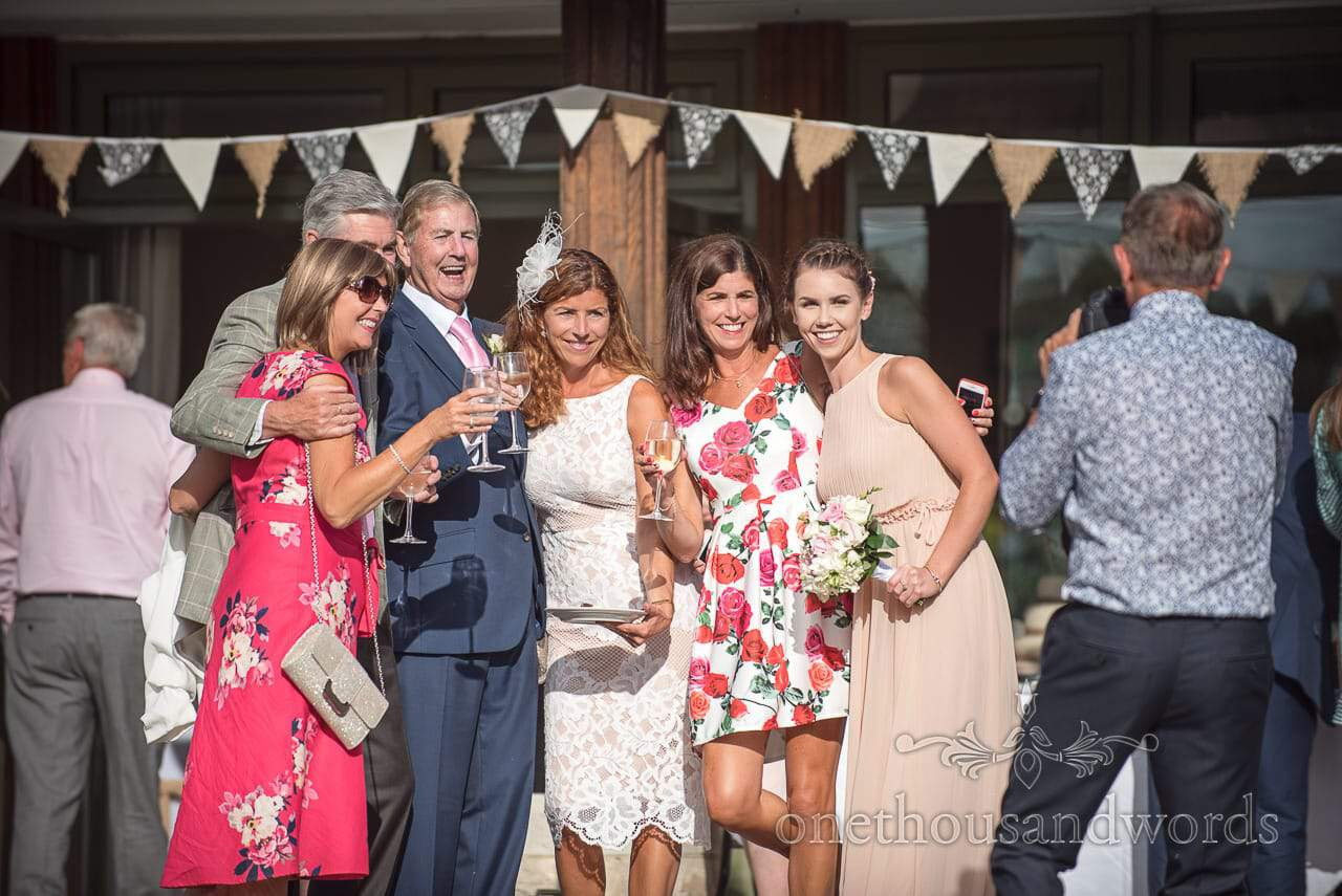 Wedding guests pose at Harmans Cross Village Hall Wedding under bunting