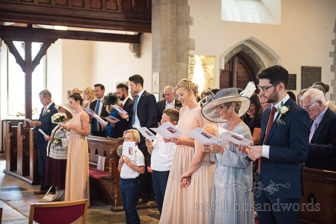 Wedding guests singing during church wedding ceremony in Swanage Dorset
