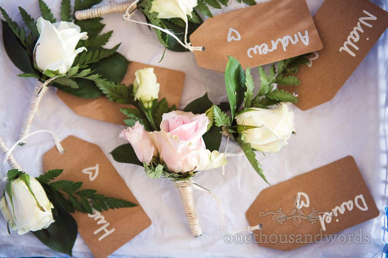 White and pink rose wedding rose button holes with brown paper name tags