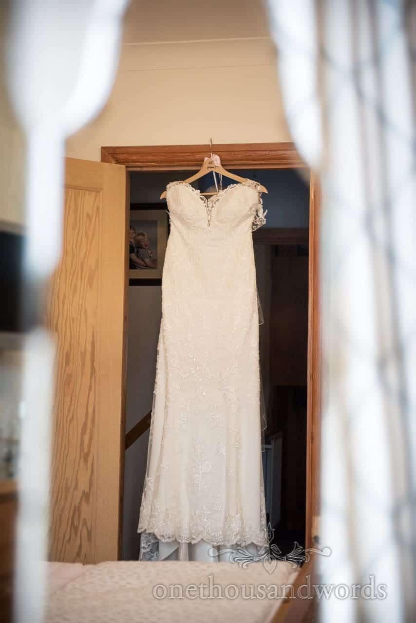 White wedding dress hangs in doorway on wedding morning in Dorset in mirror