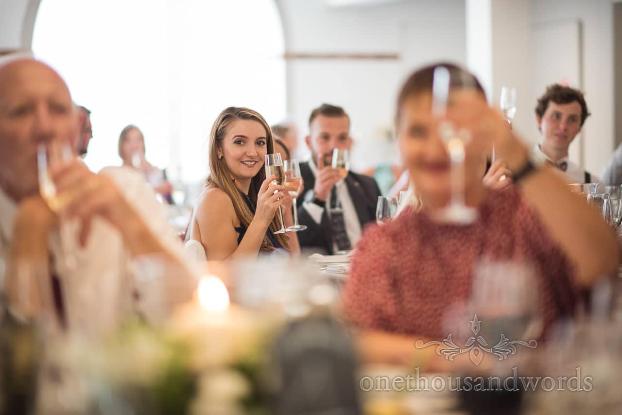 Beautiful wedding guest raises champagne glass during wedding speech toasts
