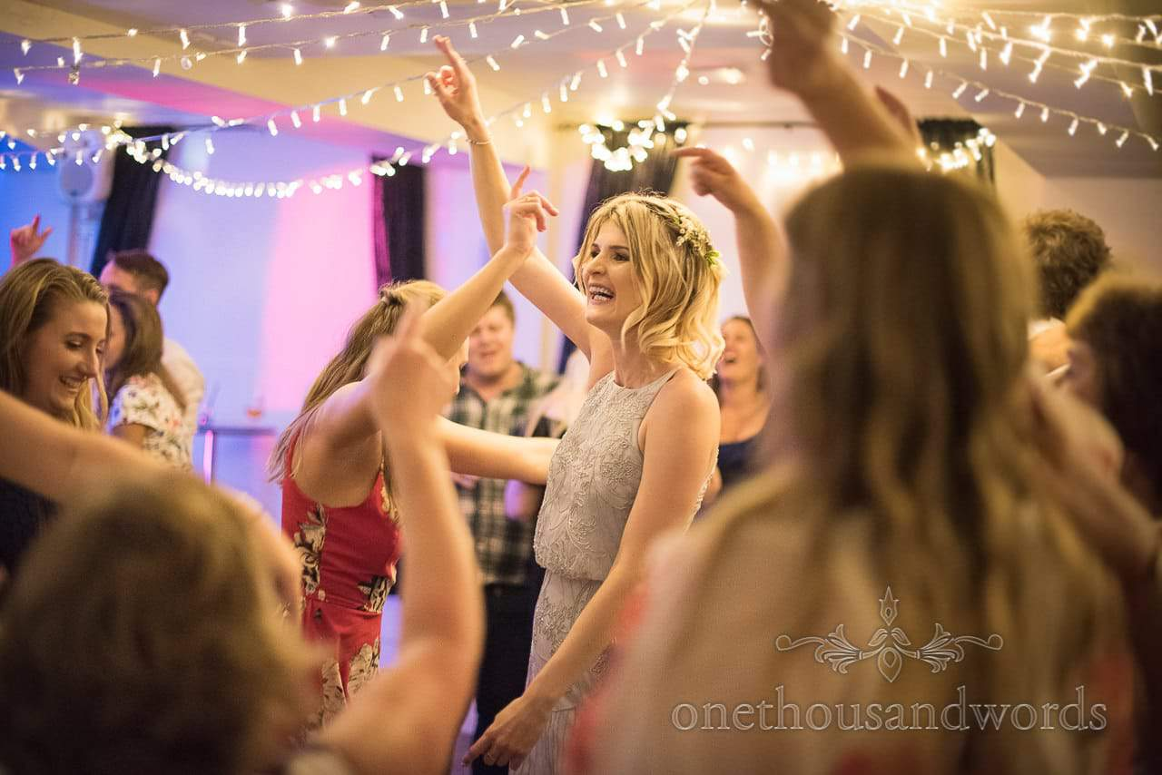 Blonde bridesmaid and wedding guest dance under fairy lights at The Italian Villa