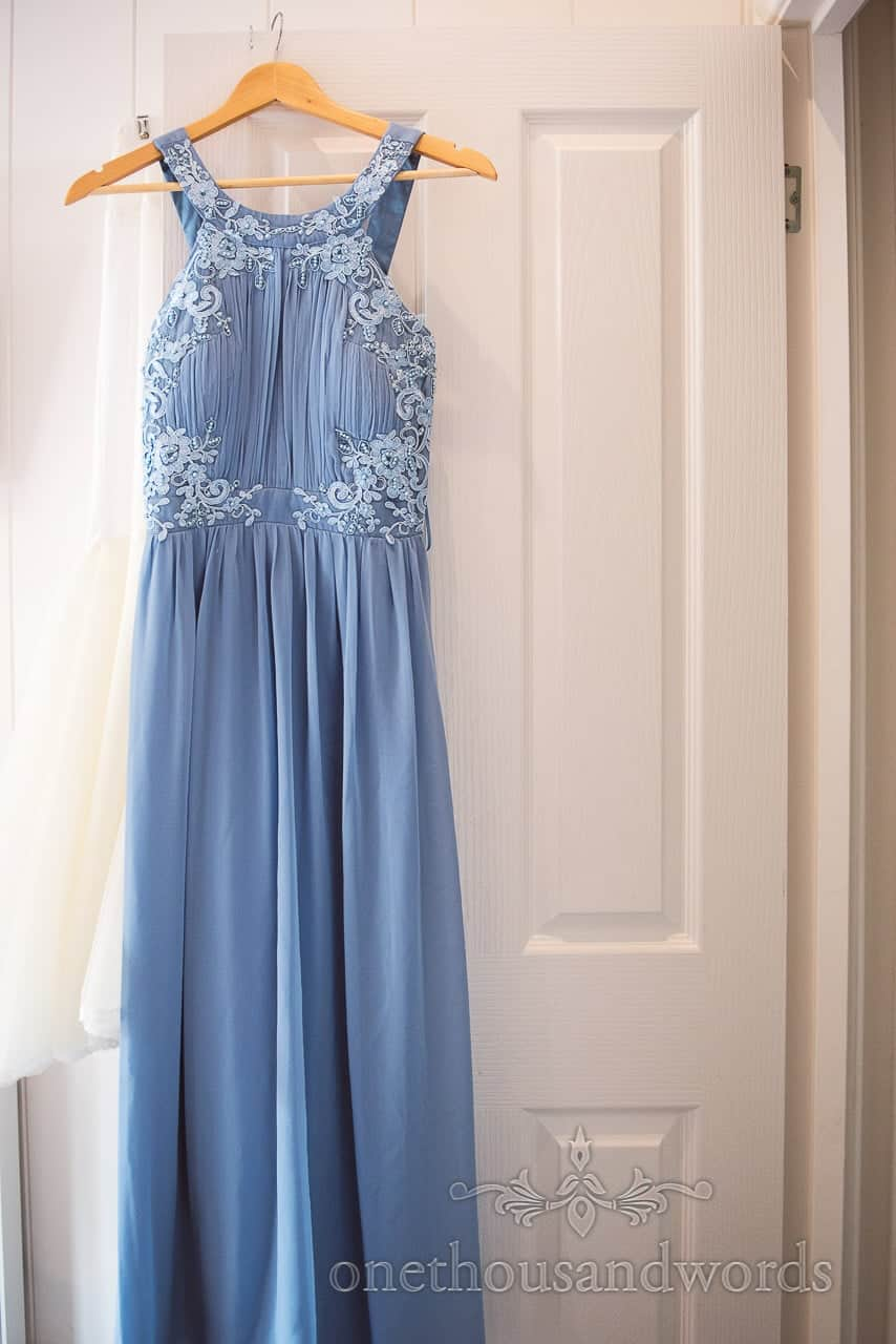Blue bridesmaid dress with lace flower details during wedding preparations