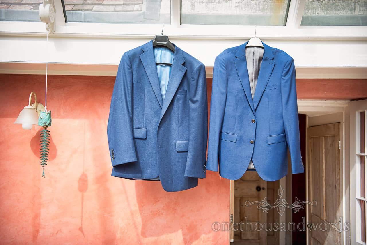 Blue wedding jackets hang in conservatory before garden wedding