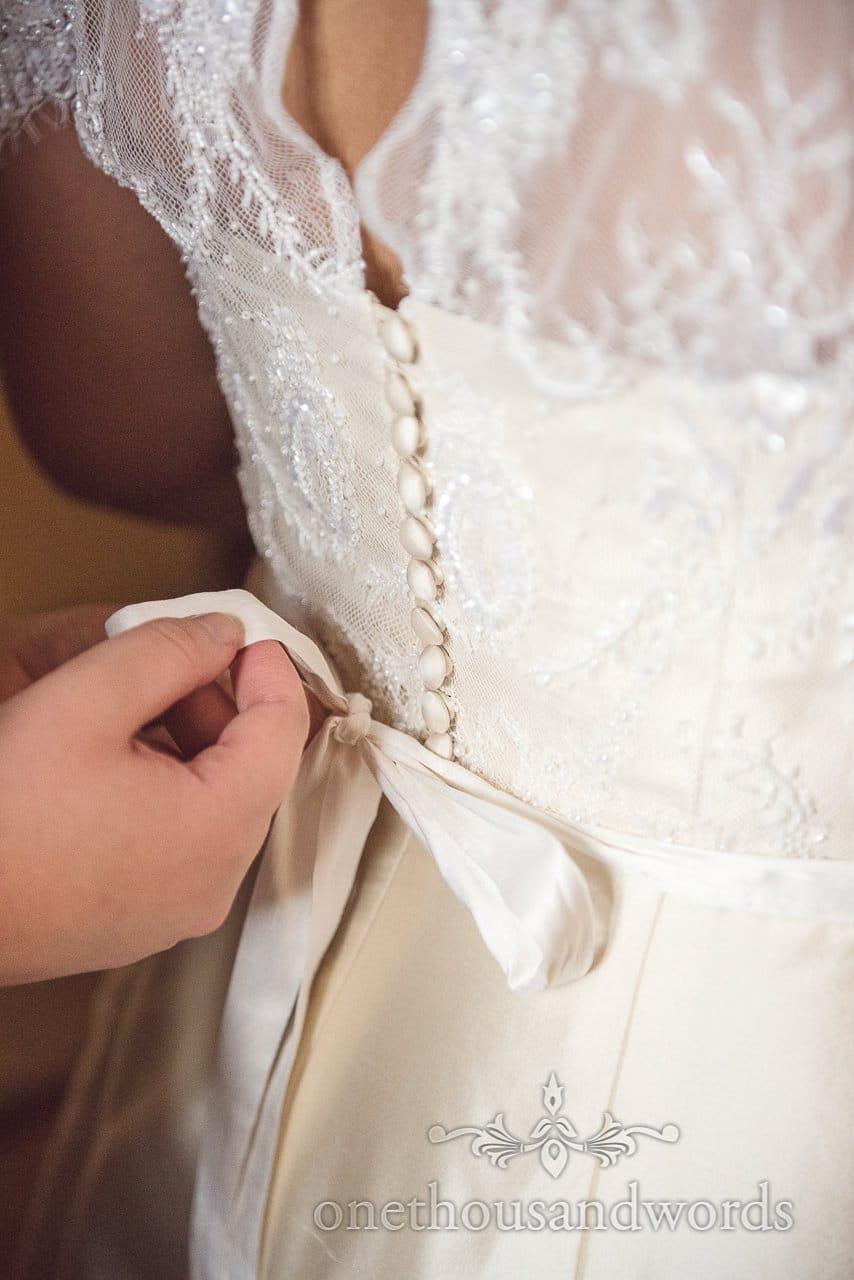 Bow tied on custom wedding dress before Garden Wedding