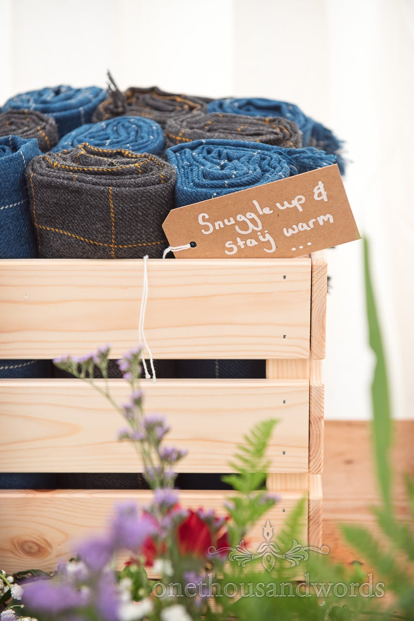 Box of blankets with message for guests at Dorset garden wedding