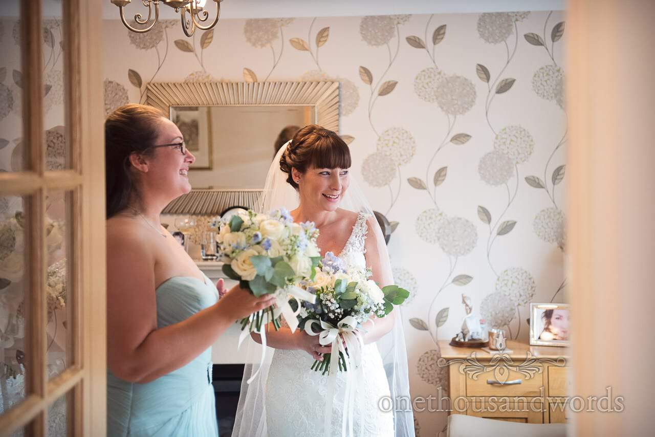 Bride and bridesmaid with bouquets on morning of Canford School Wedding