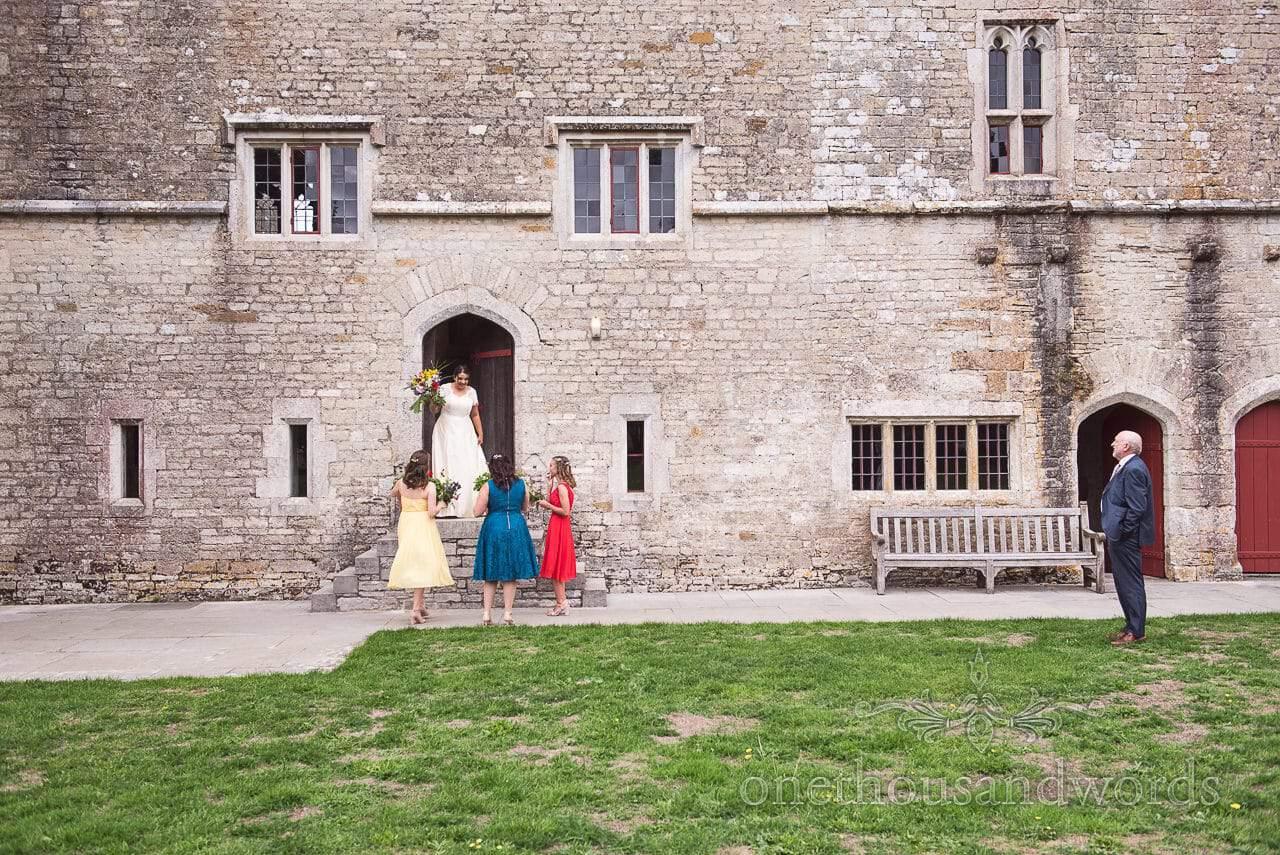 Bride and bridesmaids gather outside castle before Dorset Garden Wedding