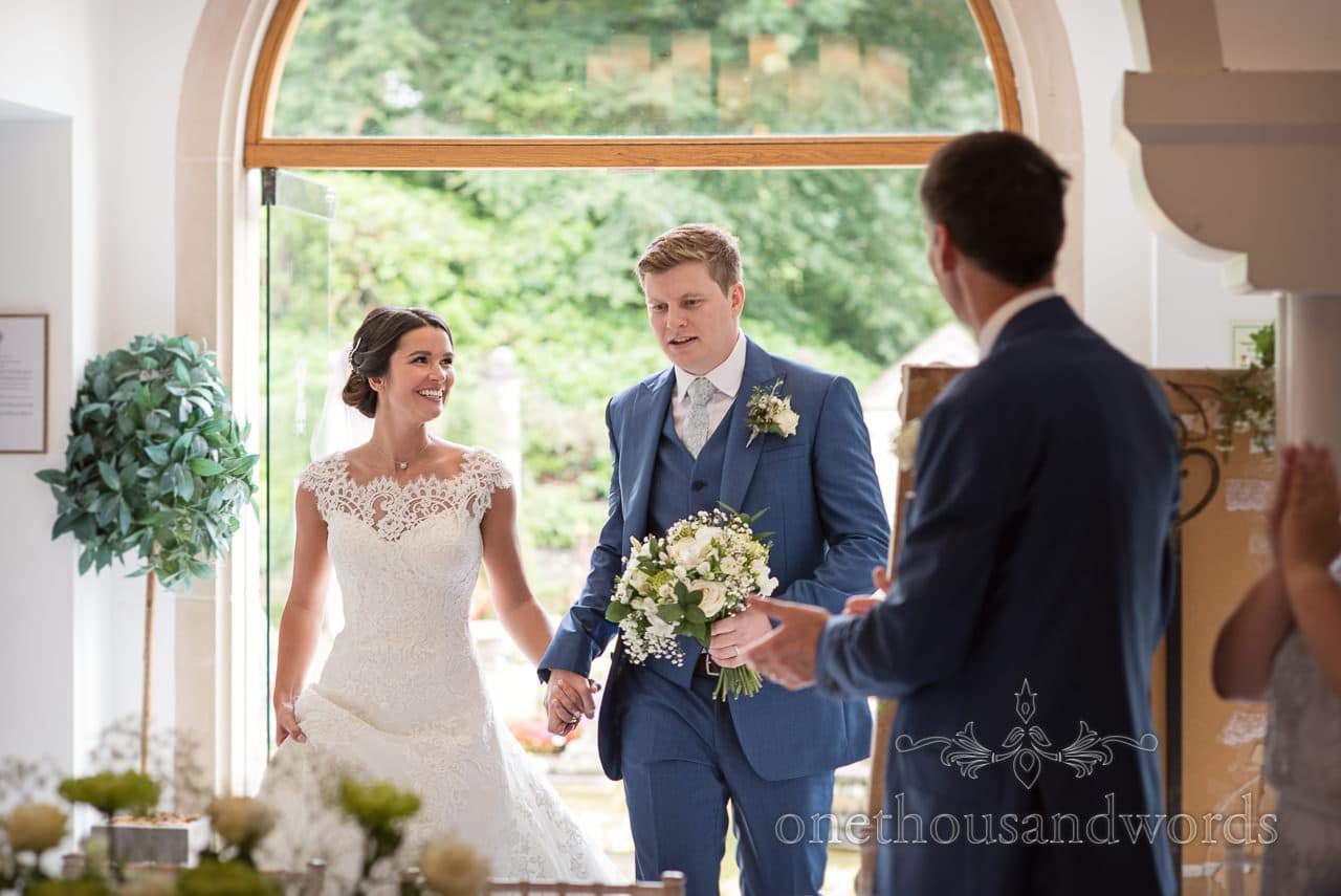 Bride and groom are applauded into wedding breakfast at Italian Villa Wedding venue