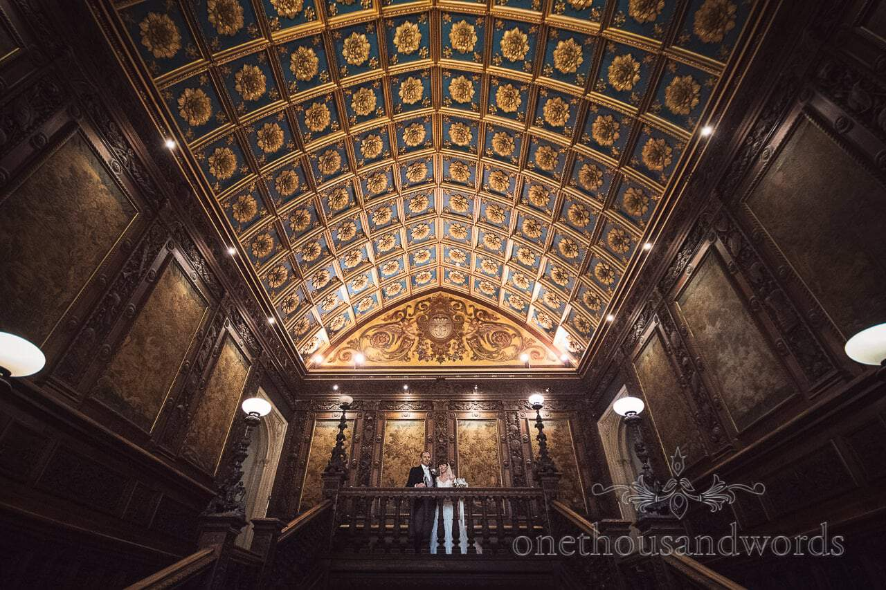 Bride and groom atop grand staircase at Canford School Wedding Photographs