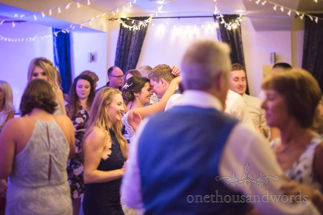 Bride and groom in amongst guests on wedding dance floor at The Italian Villa