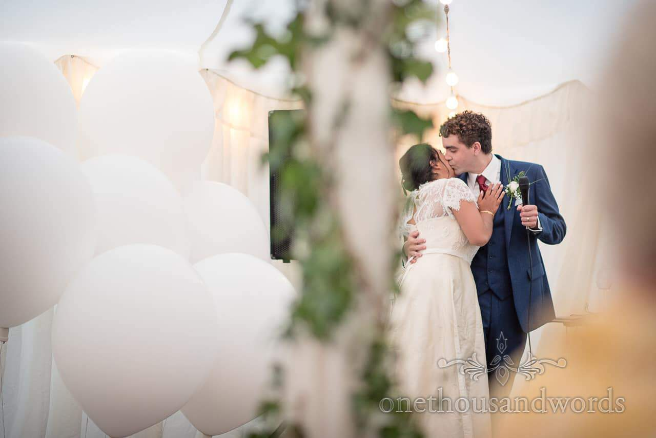 Bride and groom kiss during marquee wedding reception