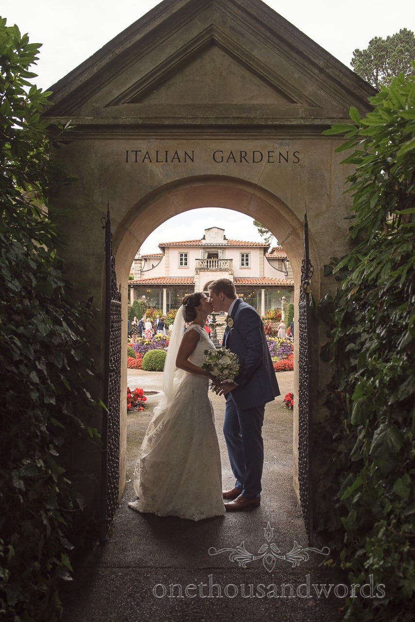 Bride and groom kiss under stone archway to the Italian Gardens at the Italian Villa