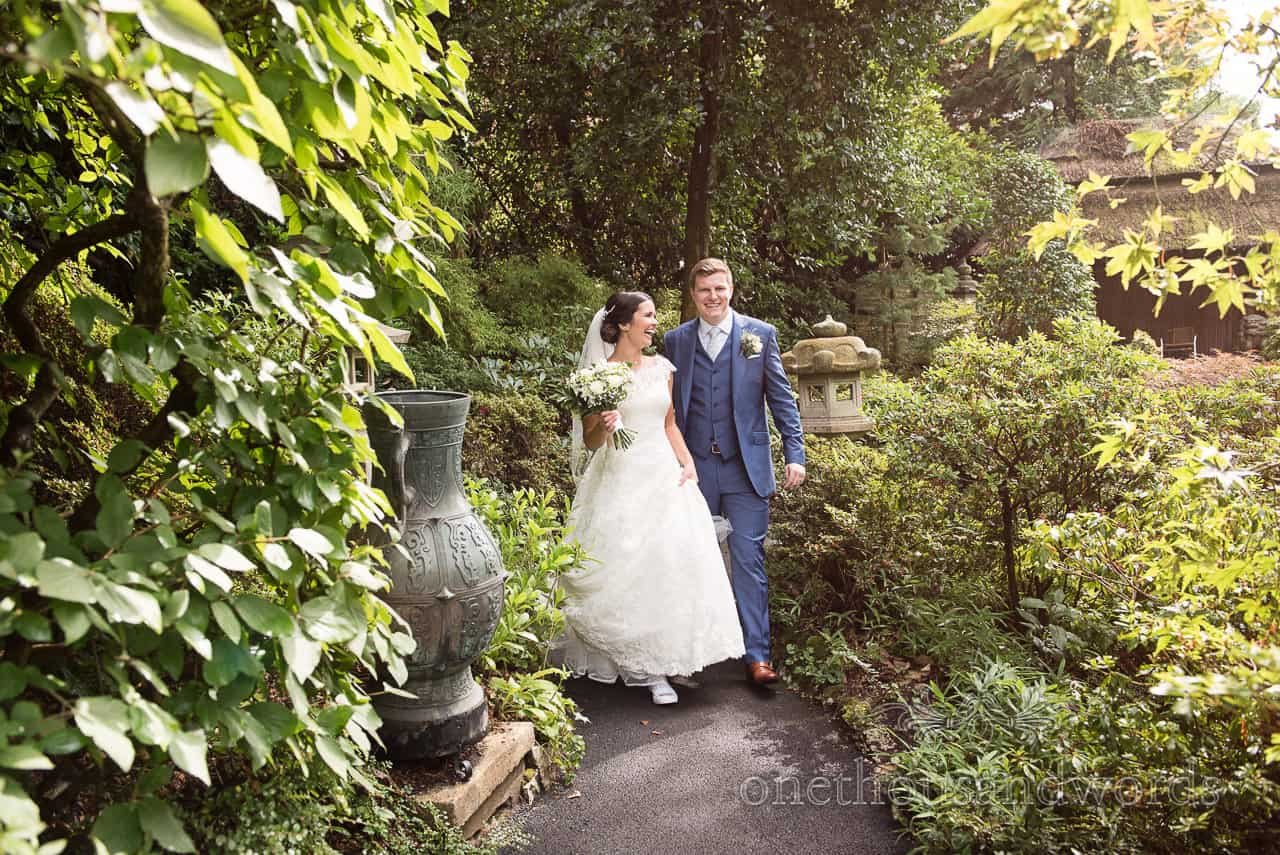 Bride and groom laugh as they walk through Japanese gardens at The Italian Villa