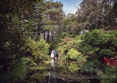 Bride and groom on stepping stones in Japanese gardens at Italian Villa Wedding
