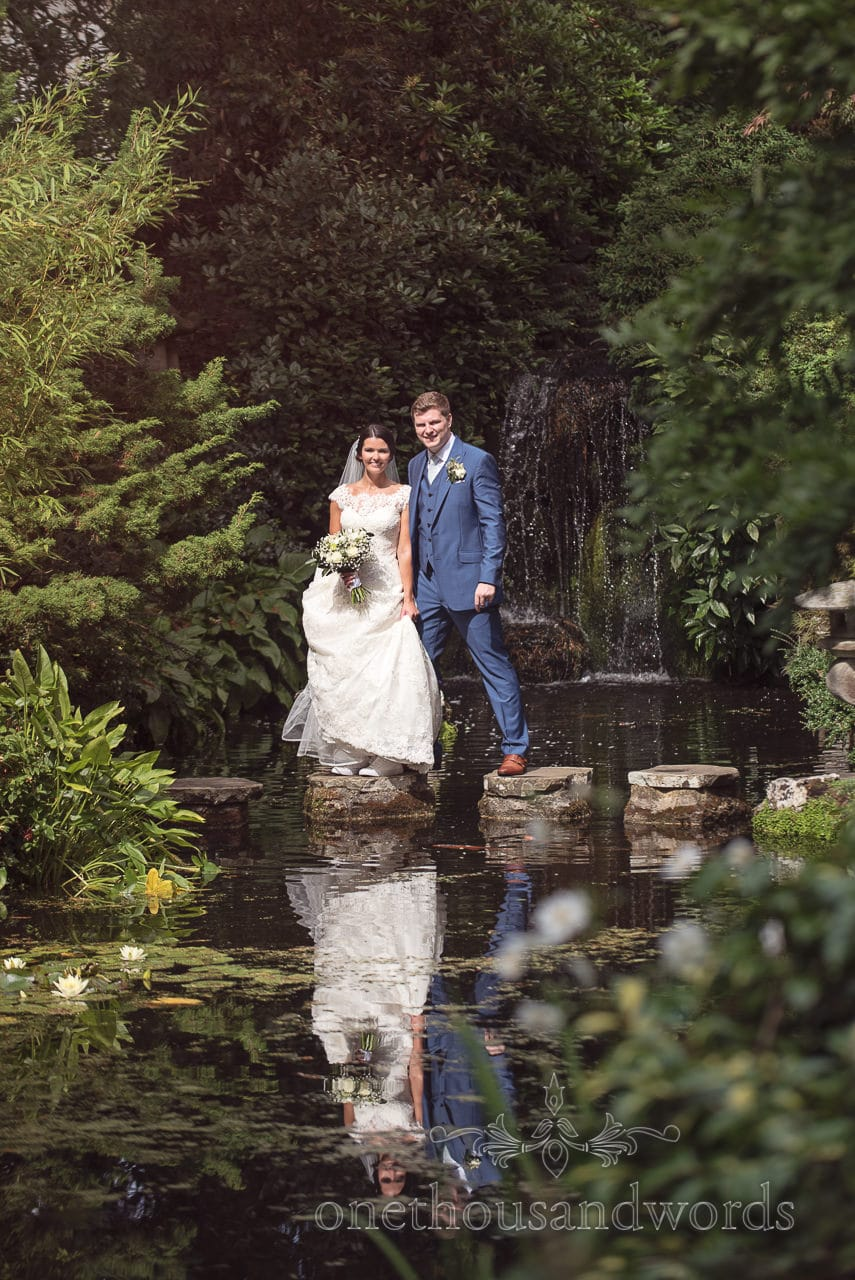 Bride and groom on stepping stones with waterfall at Italian Villa Wedding venue