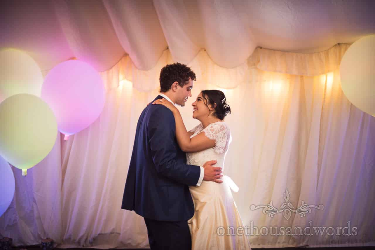 Bride and groom take first dance at marquee wedding reception