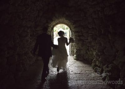 Bride and groom walk through stone cave at Italian Villa Wedding venue in Dorset