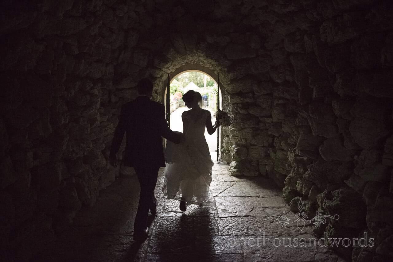 Bride and groom walk through stone cave at Italian Villa Wedding venue in Dorset