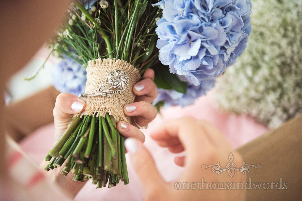 Bride attaches special brooch to wedding bouquet during morning preparations