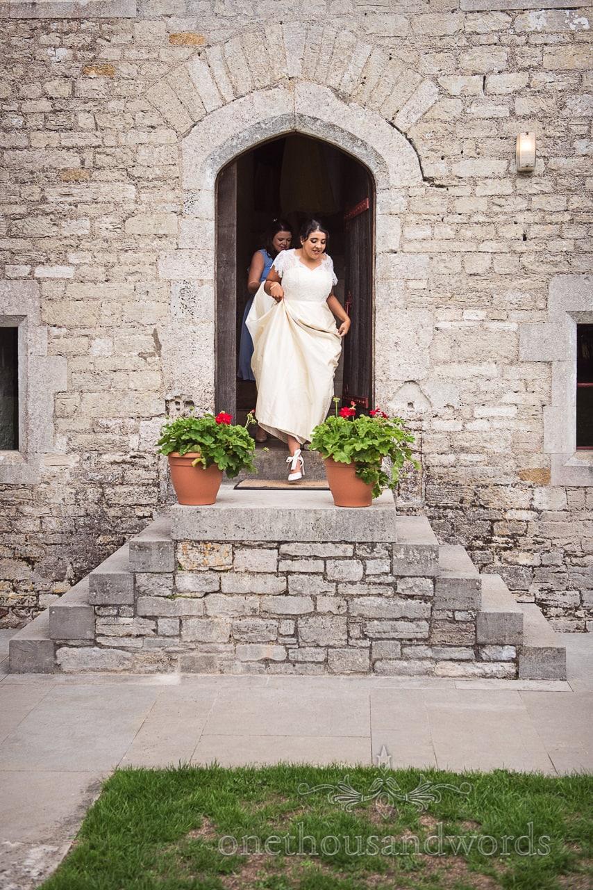 Bride comes out of castle door before Dorset Garden Wedding