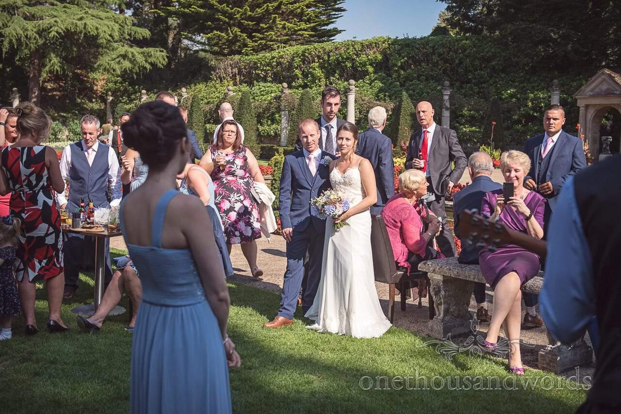 Bride and groom enjoy performance in garden at Italian Villa Wedding venue photos