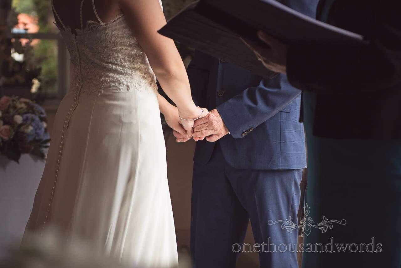 Bride and groom hold hands during civil ceremony at Italian Villa Wedding Venue Photos