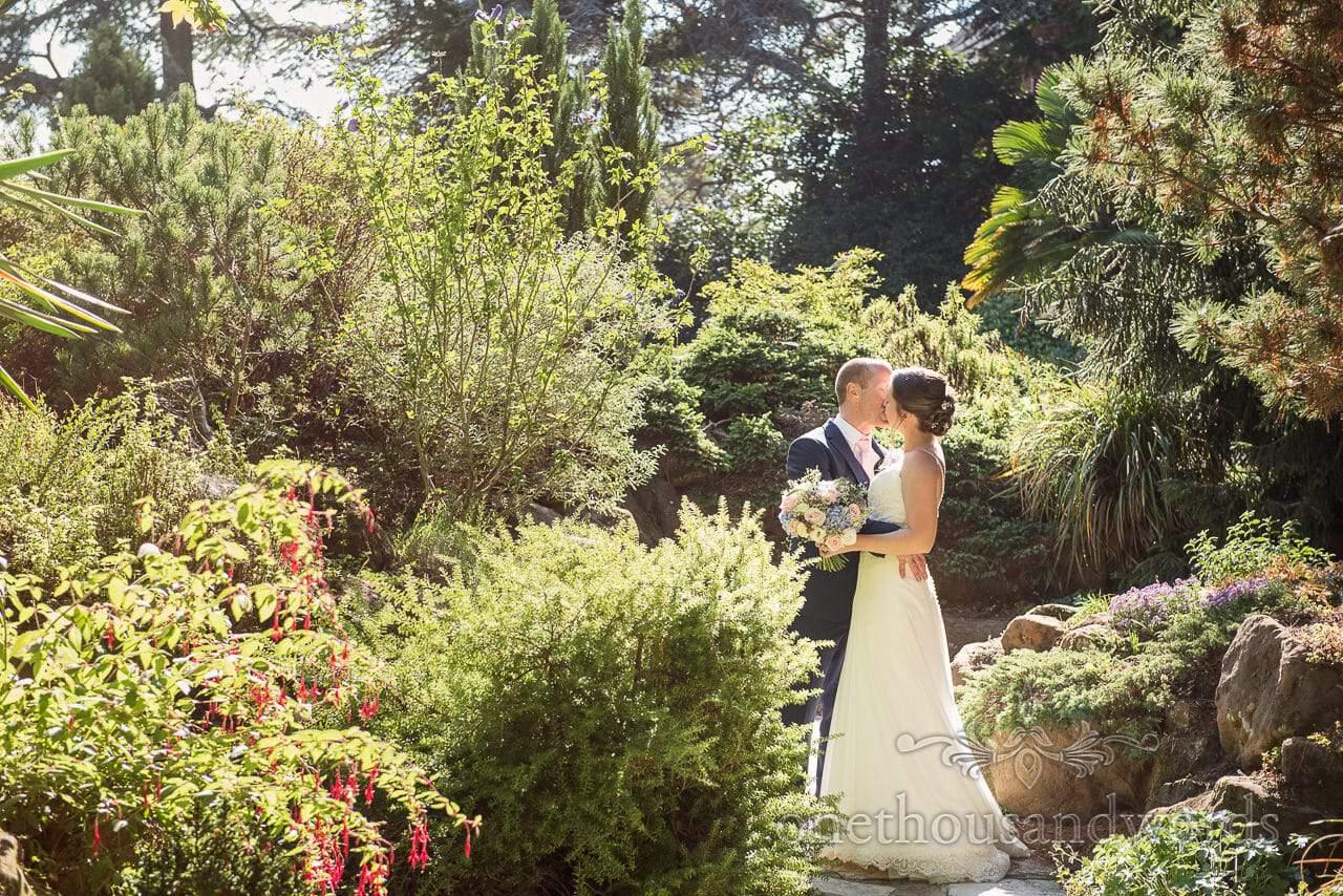 Bride and groom kiss in sunlit garden at Compton Acres