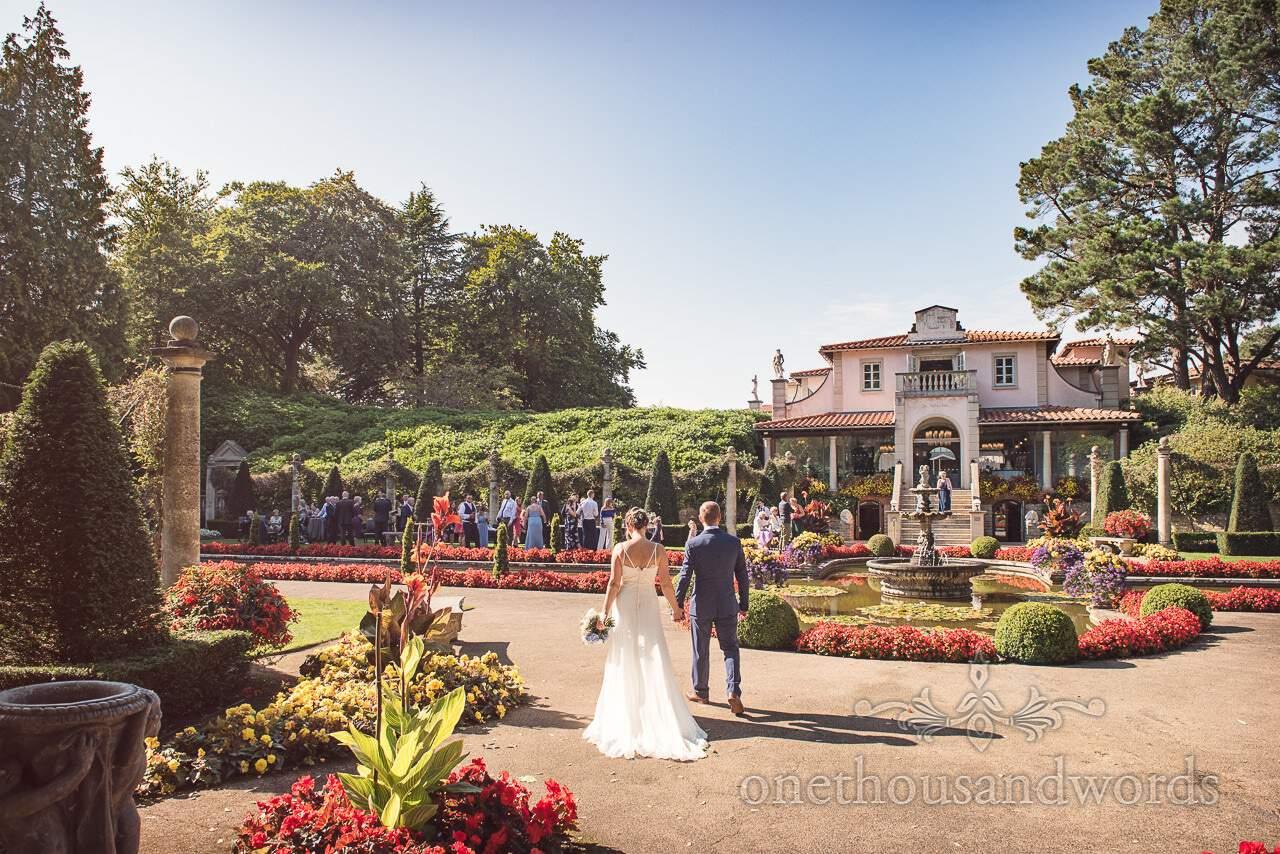 Bride and groom walk hand in hand in garden at the Italian Villa Wedding
