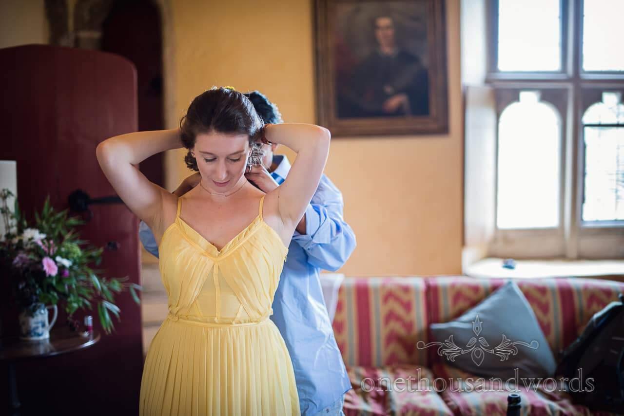 Bride helps bridesmaid with necklace before Garden Wedding