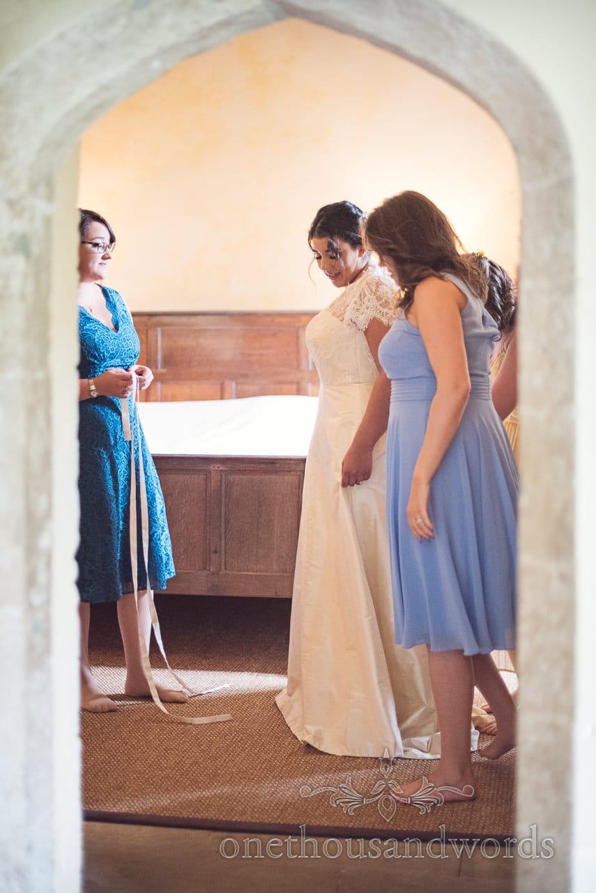 Bride in custom wedding dress through doorway at Woodsford castle