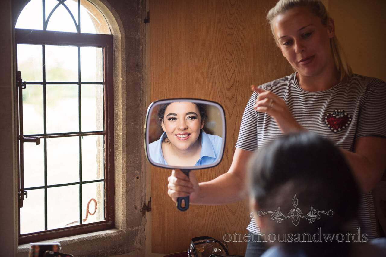 Bride in mirror during morning preparations at Woodsford castle